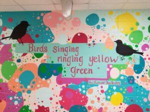 Rockwell Elementary School mural featuring Niedecker poetry: Birds singing ringing yellow green.